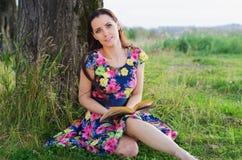 Bella donna che legge un libro nella sosta Fotografie Stock