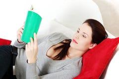 Bella donna che legge un libro su un sofà. Immagine Stock Libera da Diritti
