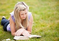 Bella donna che legge un libro in una sosta Fotografie Stock