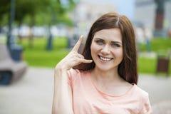 Bella donna che lo rende ad una chiamata gesto Fotografie Stock