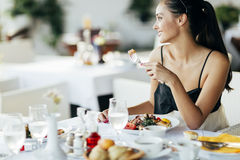 Bella donna che mangia pasto in ristorante Fotografia Stock