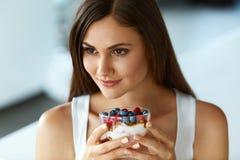 Bella donna che mangia yogurt, le bacche e cereale Dieta sana Fotografia Stock