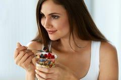 Bella donna che mangia yogurt, le bacche e cereale Dieta sana Fotografia Stock Libera da Diritti