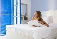 Bella donna che mette sul letto nella camera da letto Immagini Stock