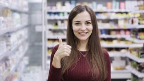 Bella donna che mostra i pollici sul segno nel supermercato archivi video