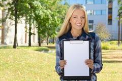 Bella donna che mostra lavagna per appunti con copyspace nel parco di autunno Immagine Stock