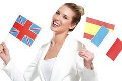 Bella donna che mostra le bandiere internazionali Fotografie Stock Libere da Diritti