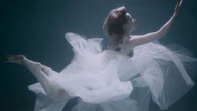 Bella donna che nuota underwater in vestito elegante bianco video d archivio