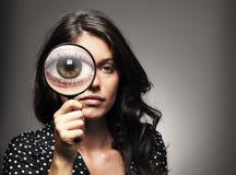 Bella donna che osserva tramite una lente d'ingrandimento Fotografie Stock