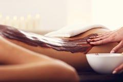 Bella donna che ottiene massaggio del cioccolato in stazione termale Immagine Stock