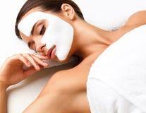 Bella donna che ottiene trattamento della stazione termale. Maschera cosmetica sul fronte. La SK Immagine Stock