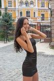 Bella donna che parla su un telefono cellulare su una via della città Immagine Stock