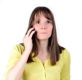 Bella donna che parla sul cellulare e che è nella scossa delle notizie Fotografia Stock