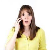 Bella donna che parla sul cellulare e che è nella scossa delle notizie Fotografie Stock