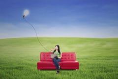 Bella donna che pensa sul sofà rosso sotto la lampada all'aperto Fotografie Stock Libere da Diritti
