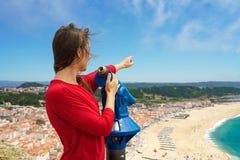 Bella donna che per mezzo del binocolo pagato della moneta sull'alta collina e sullo sguardo Immagine Stock