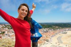 Bella donna che per mezzo del binocolo pagato della moneta sull'alta collina e sullo sguardo Fotografie Stock Libere da Diritti
