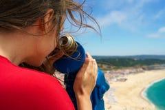 Bella donna che per mezzo del binocolo pagato della moneta sull'alta collina e sullo sguardo Immagini Stock Libere da Diritti
