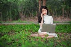 Bella donna che per mezzo del computer portatile e chiamando con il telefono cellulare in Th Immagine Stock