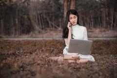 Bella donna che per mezzo del computer portatile e chiamando con il telefono cellulare in Th Fotografia Stock