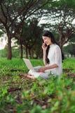Bella donna che per mezzo del computer portatile e chiamando con il telefono cellulare in Th Fotografie Stock