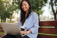 Bella donna che per mezzo del computer portatile mentre sedersi rilassata su Ben di legno Fotografia Stock Libera da Diritti