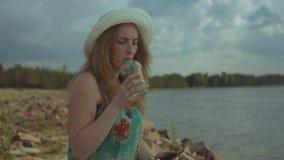 Bella donna che per mezzo del telefono cellulare app alla spiaggia archivi video