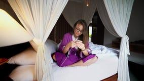 Bella donna che per mezzo del telefono a letto che dirige casa collegata astuta con il app mobile archivi video
