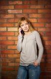 Bella donna che per mezzo dello smartphone alta tecnologia contro il muro di mattoni. Fotografia Stock