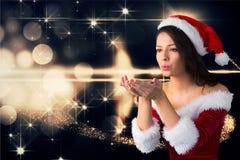 Bella donna che porta il costume di Santa che soffia un bacio contro il backgroun digitalmente generato di natale fotografia stock