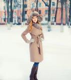 Bella donna che porta un rivestimento e un cappello del cappotto sopra neve nell'inverno immagini stock