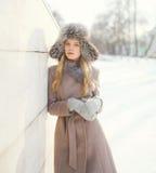 Bella donna che porta un rivestimento e un cappello del cappotto sopra neve nell'inverno fotografie stock libere da diritti