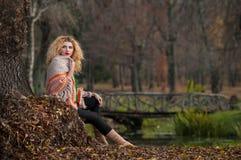 Bella donna che posa nel parco durante la stagione di autunno. Ragazza bionda che indossa blusa verde e grande posa dello scialle  Fotografia Stock