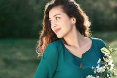 Bella donna che posa su una radura nel parco della città, nel sole luminoso e nelle ombre sull'erba fotografie stock