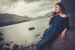 Bella donna che posa sulla riva di un lago selvaggio, con le montagne sui precedenti fotografia stock