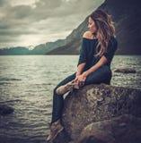 Bella donna che posa sulla riva di un lago selvaggio, con le montagne sui precedenti Immagine Stock Libera da Diritti