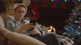 Bella donna che pratica il surfing Internet sullo smartphone nella notte del nuovo anno dall'albero decorato archivi video