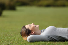 Bella donna che riposa sull'erba in un parco Immagine Stock Libera da Diritti
