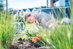 Bella donna che rispetta ecologia che prende cura delle sue piante fuori della casa fotografie stock