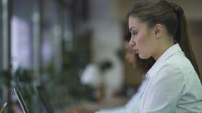 Bella donna che scrive sul computer portatile, lavorante al progetto di affari con il fronte messo a fuoco archivi video
