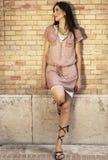 Bella donna che si appoggia contro un muro di mattoni fotografie stock
