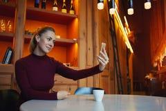 Bella donna che si fotografa sul telefono delle cellule mentre sedendosi nel ristorante moderno con l'interno di lusso, Fotografia Stock Libera da Diritti