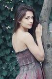 Bella donna che si leva in piedi albero vicino fotografia stock libera da diritti