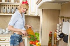 Bella donna che si leva in piedi nella cucina Fotografia Stock