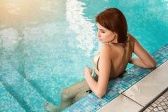 Bella donna che si rilassa al poolside di lusso Ragazza allo stagno della località di soggiorno di stazione termale di viaggio Fotografia Stock Libera da Diritti