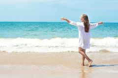 Bella donna che si rilassa e che gode del vento in suoi capelli, nel suono delle onde, nell'odore dell'oceano sulla spiaggia dall Fotografia Stock Libera da Diritti