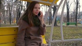 Bella donna che si rilassa su un'oscillazione e che tiene Smart Phone Fuoco selettivo stock footage