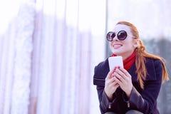 Bella donna che si siede alla via che tiene suo sorridere del telefono cellulare Immagine Stock