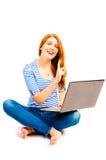 Bella donna che si siede con un computer portatile Fotografia Stock