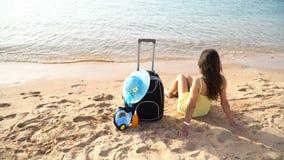 Bella donna che si siede con una valigia sulla spiaggia soleggiata video d archivio